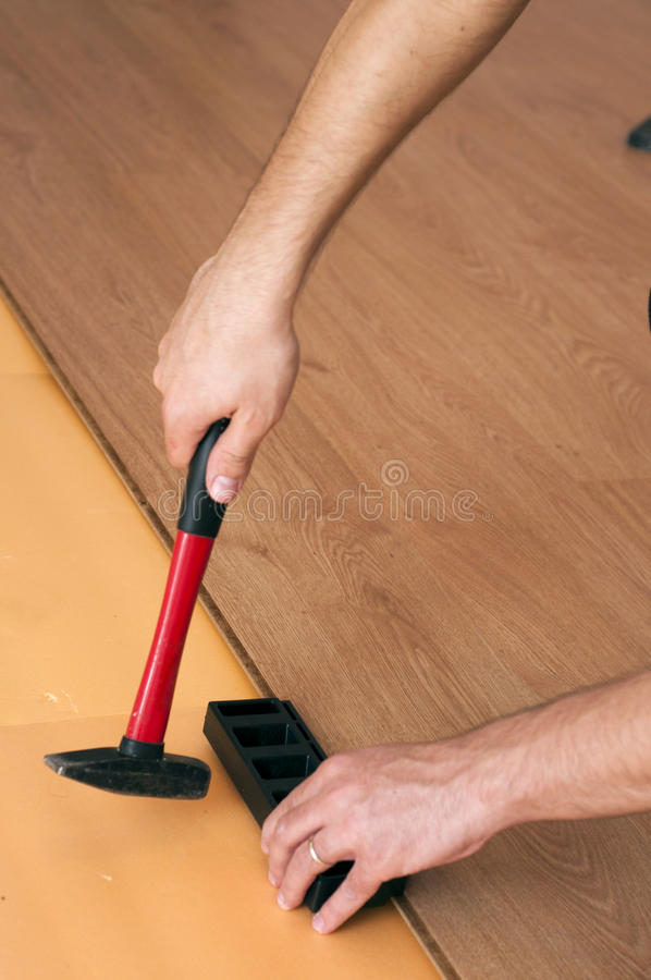 Hands of a worker mounting laminated floor royalty free stock photos