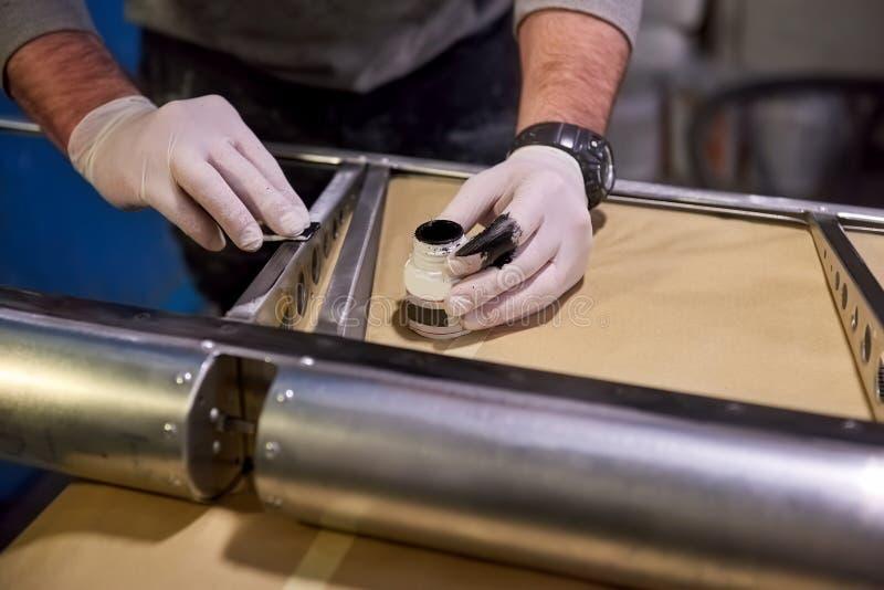 Hands of worker priming metal. stock images