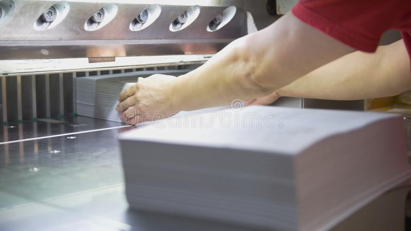 Hands of worker takes away reams of paper from cutting maschine stock photography