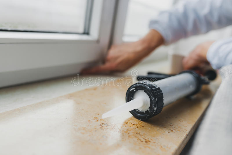 Hands of worker using a silicone tube for repairing of window royalty free stock images