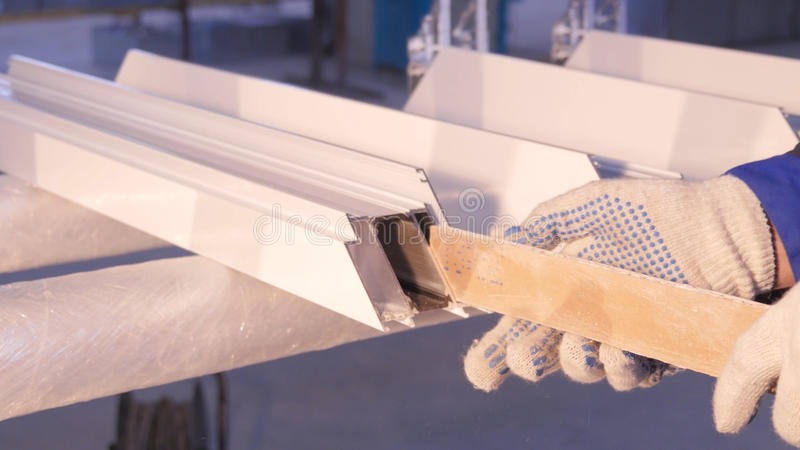 Hands of worker using a silicone tube for repairing of window indoor. Window details from aluminum. Construction worker royalty free stock image