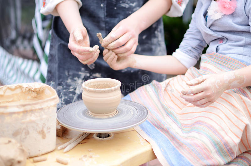 Hands working on throwing wheel, master class of studio pottery stock images