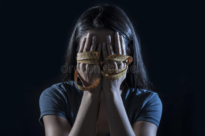 Hands wrapped in tailor measure tape covering face of young depressed and worried girl suffering anorexia or bulimia nutrition dis. Close up hands wrapped in stock photo