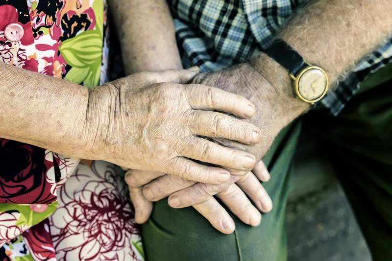 Hands with wrinkles of elderly couple, holding hands of seniors together close-up, concept of relationships, marriage stock photography