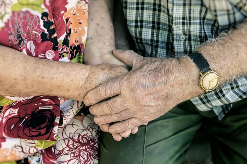 Hands of elderly couple, holding hands of seniors together close-up, concept of relationships, marriage and old people. Hands wrinkles of elderly couple, holding stock photo