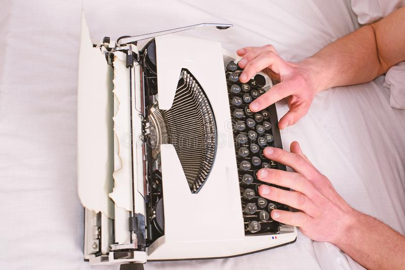 Hands writer bed white bedclothes working on new book. Writer author used to old fashioned machine instead of digital. Gadget. Create new chapter use typewriter stock photography