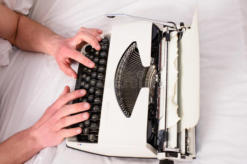 Hands writer bed white bedclothes working on new book. Writer author used to old fashioned machine instead of digital. Gadget. Create new chapter use typewriter stock photos
