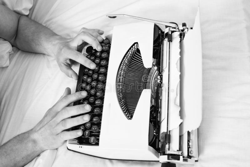 Hands writer bed white bedclothes working on new book. Writer author used to old fashioned machine instead of digital. Gadget. Create new chapter use typewriter royalty free stock images