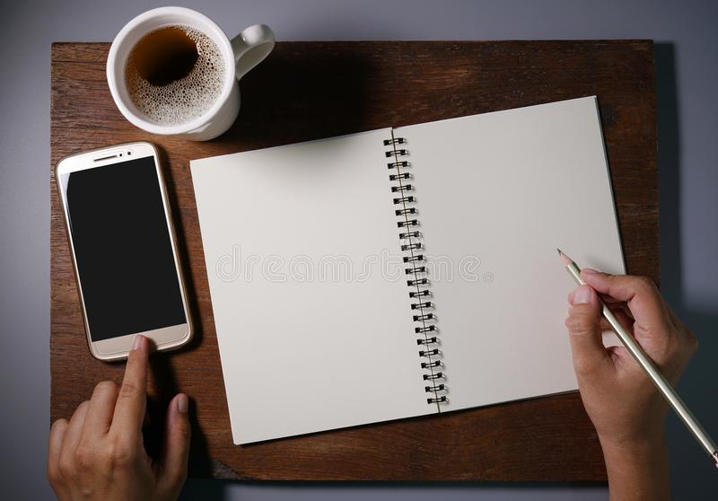 Hands writing in blank notebook by pencil and one hands touch smartphone for searching data. Woman hands writing in blank notebook by pencil and one hands touch stock image