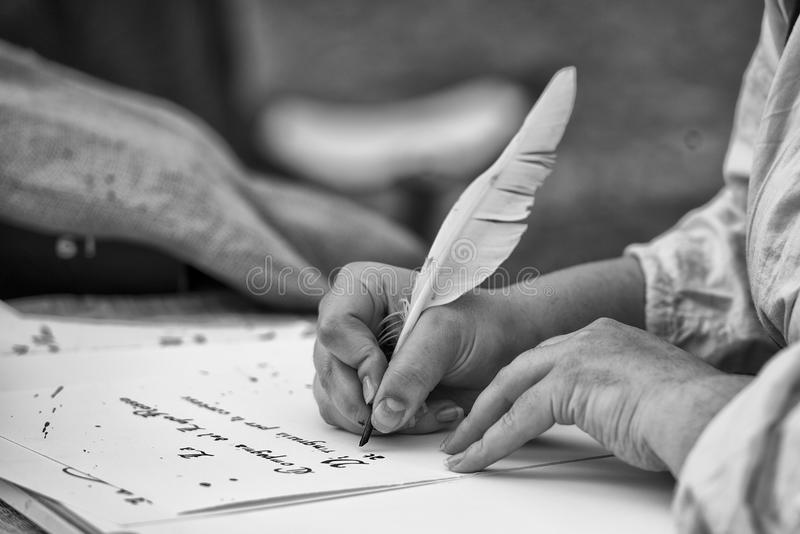 Hands writing a letter with a plume. Hands while writing a letter with a plume in black and white stock photography