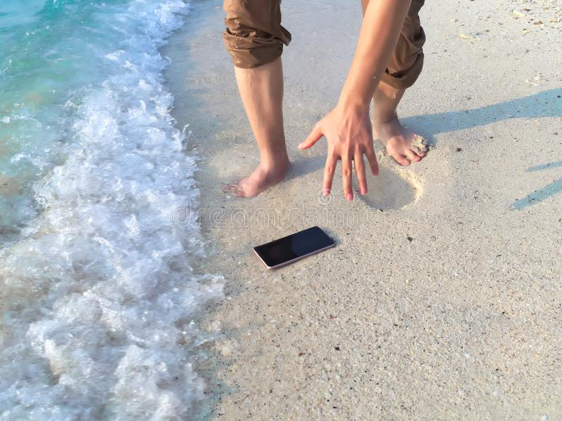 Hands of young Asian man dropping mobile smart phone on tropical sandy beach. Accident and insurance electronic equipment concept royalty free stock image