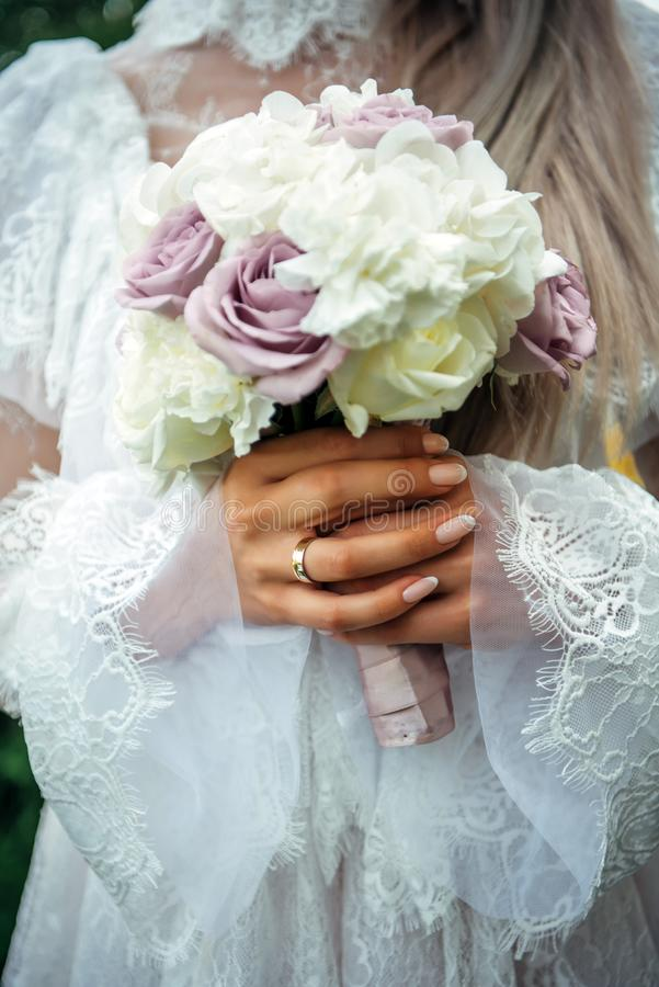 Hands of young bride holding beautiful wedding bouquet. Bride`s hand with a wedding ring on her finger. Bride in vintage white stock image
