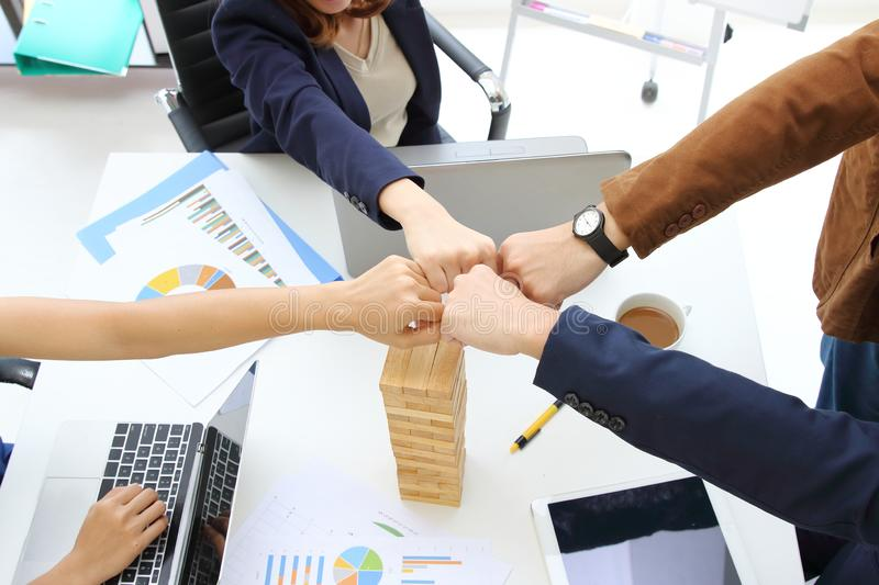 Hands of young business people giving fist bump together to greeting complete dealing in office. Success and teamwork concept. stock photography