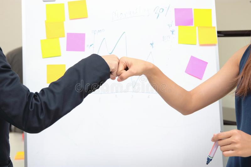 Hands of young business people giving fist bump together to greeting complete dealing in office. Success and teamwork concept royalty free stock photography