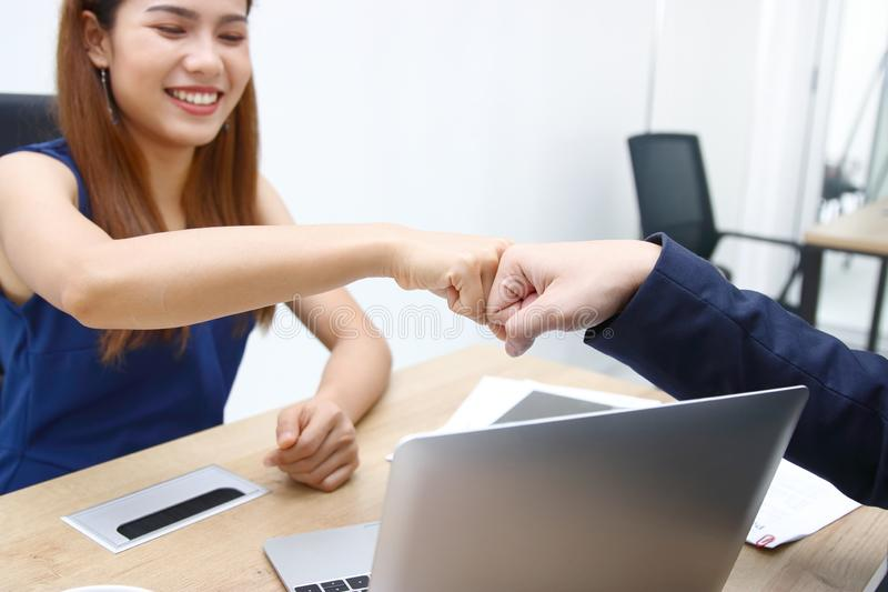 Hands of young business people giving fist bump together to greeting complete dealing in office. Success and teamwork concept stock photo