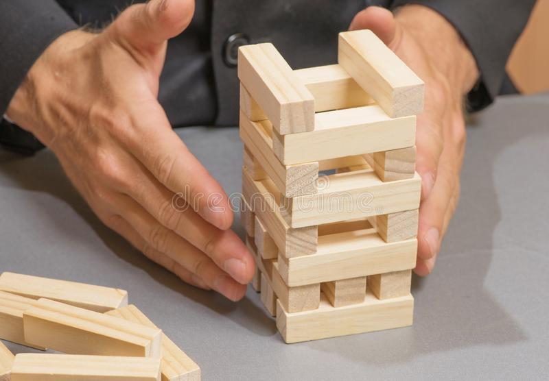 Hands of a young businessman building towers of wooden blocks, business strategy and planning, risks and insurance royalty free stock photo