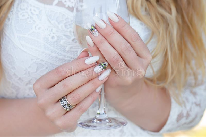 Hands of young caucasian woman holding glass of champagne during party. Bride wearing white dress . Beautiful tender wedding manic royalty free stock images