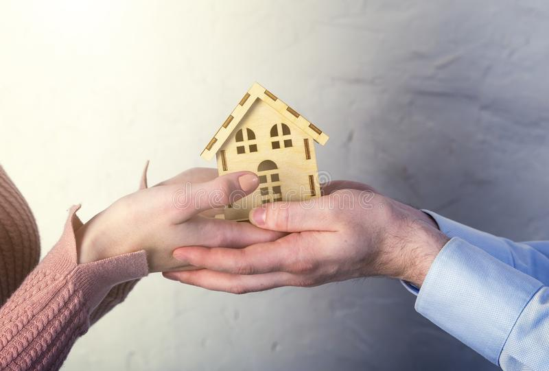 Hands of a young couple, man and woman hold wooden toy house. The concept of private housing, real estate purchase concept, royalty free stock photos