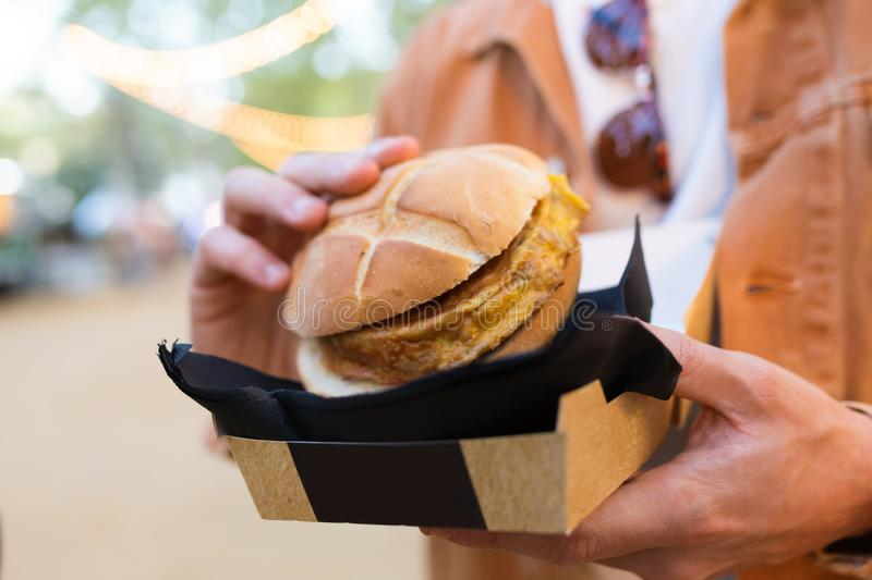 Hands of young fashion man visiting eat market and holding hamburguer in the street. Close-up of hands of young fashion man visiting eat market and holding royalty free stock images