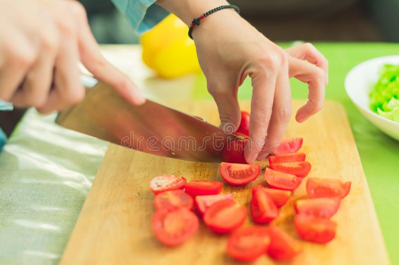 Hands of a young girl chop the cherry tomatoes on a wooden cutting board on a green table in a home setting royalty free stock images
