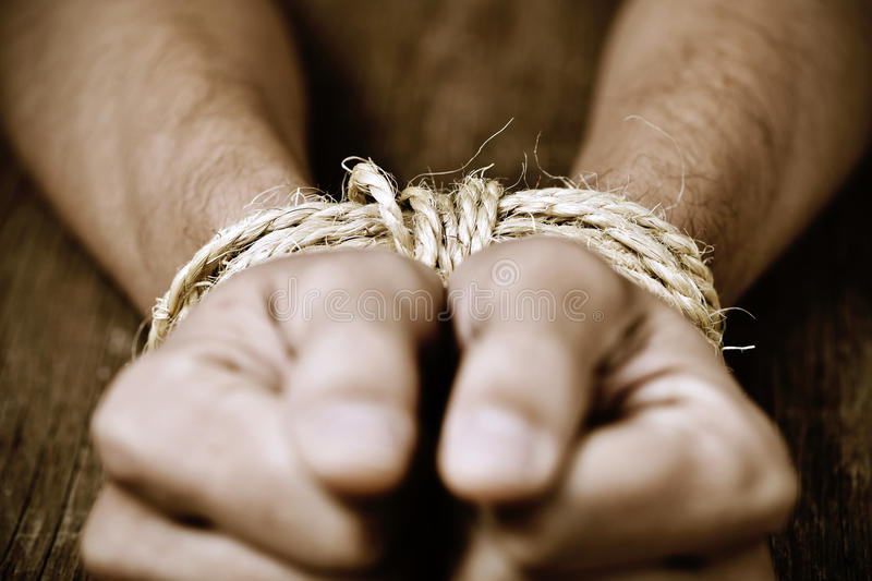 The hands of a young man tied with rope. Closeup of the hands of a young man tied with rope, as a symbol of oppression or repression, with a dramatic effect royalty free stock photos