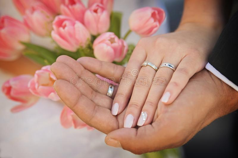 The hands of married couples and the wedding bouquet. The hands of young married couples and the wedding bouquet royalty free stock photography