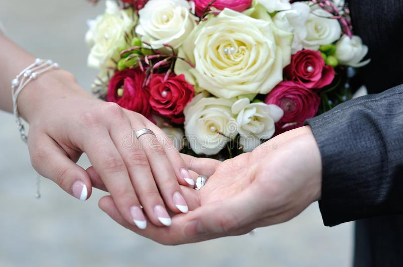 The hands of young married couples and the wedding bouquet. From roses royalty free stock photo