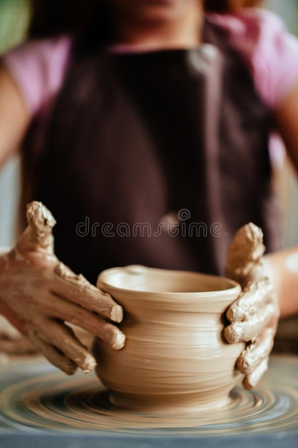 Hands of young potter, close up hands made cup on pottery wheel. Female potter working at throwing wheel at studio. Clay workshop royalty free stock photos