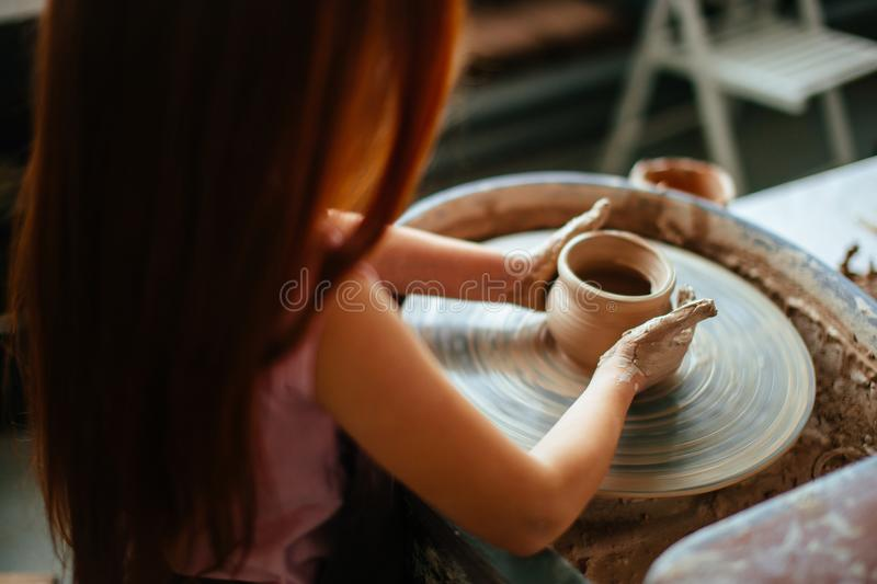 Female potter working at throwing wheel at studio. Clay workshop. Hands of young potter, close up hands made cup on pottery wheel royalty free stock photos