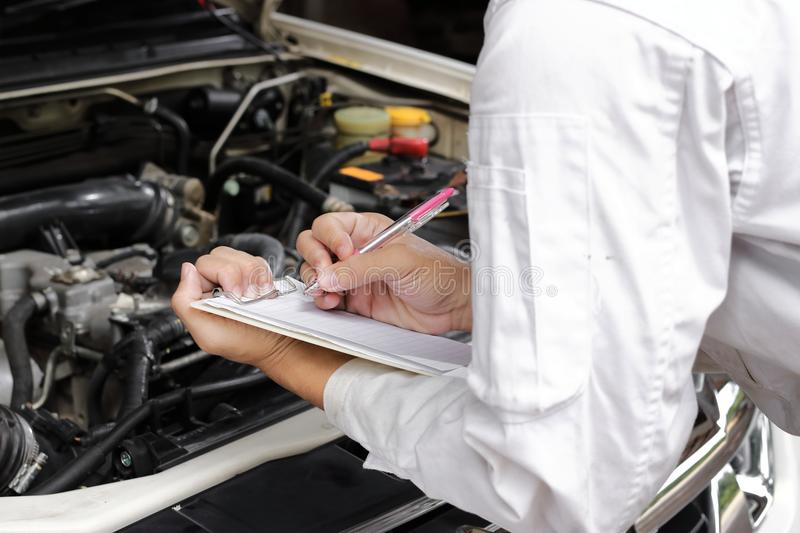 Hands of young professional mechanic in uniform writing on clipboard against car in open hood at the repair garage. Maintenance se royalty free stock photos