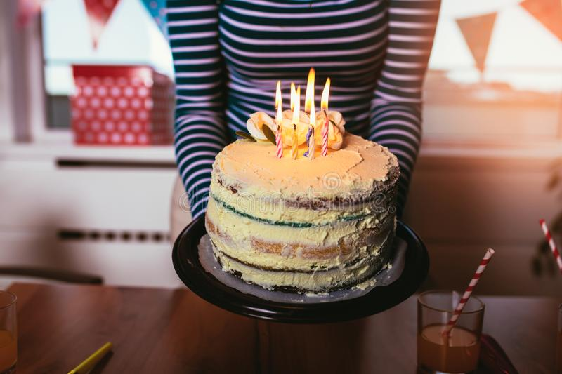 Hands of young woman holding birthday cake stock photo
