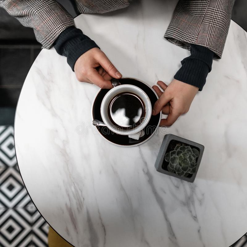 Hands of a young woman holding a black cup with hot tasty coffee in a cafe. Top view of the table. Fashion and drink. stock photos