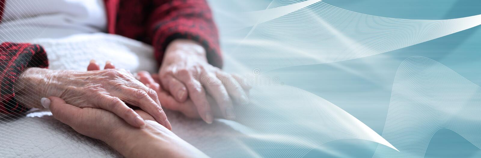 Home assistance; panoramic banner. Hands of young woman holding the hands of an elderly person; panoramic banner royalty free stock photos