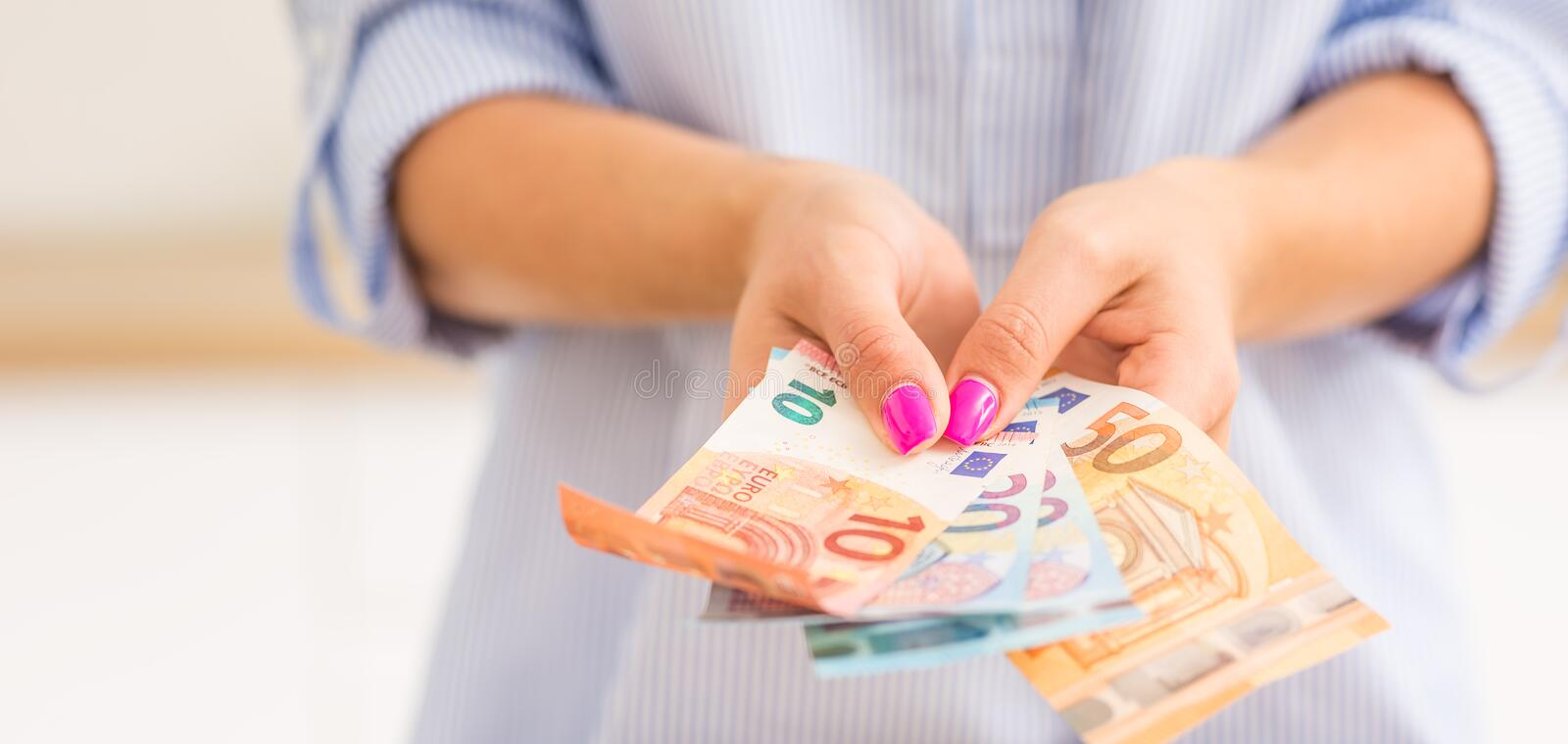 Hands of young woman holding euro banknotes royalty free stock photo