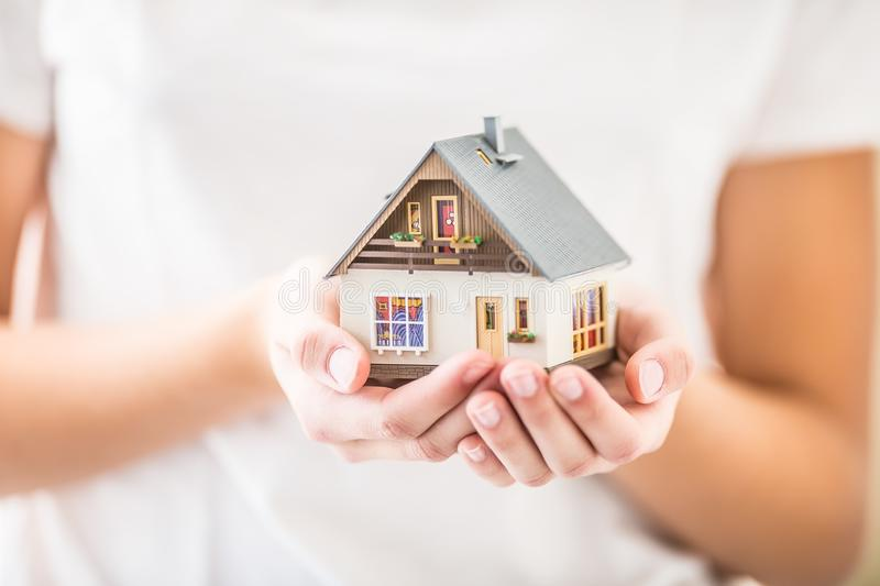 Hands of young woman holding model house royalty free stock image