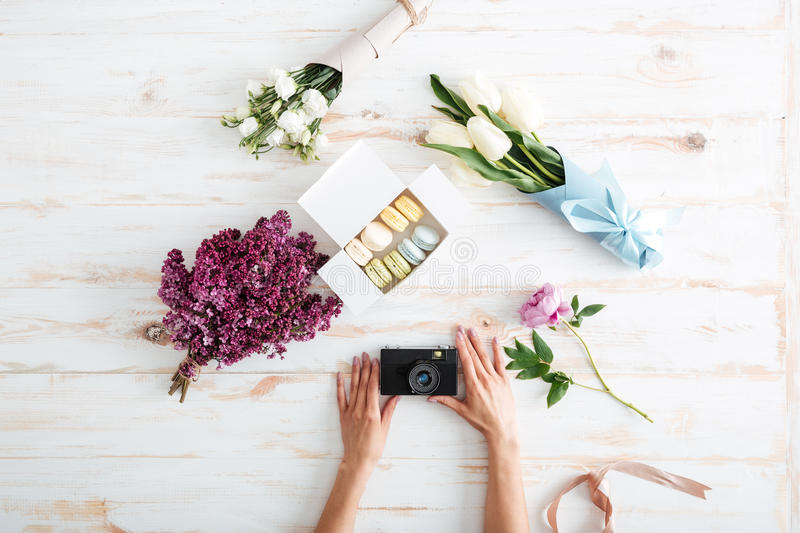 Hands of young woman holding photo camera on wooden table. With french macaroons and flowers royalty free stock photography