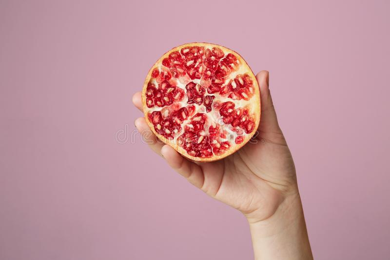 Hands of a young woman holding a red pomegranate. healthy food concept over pink background. Hands of a young woman holding a red pomegranate. healthy food stock photography
