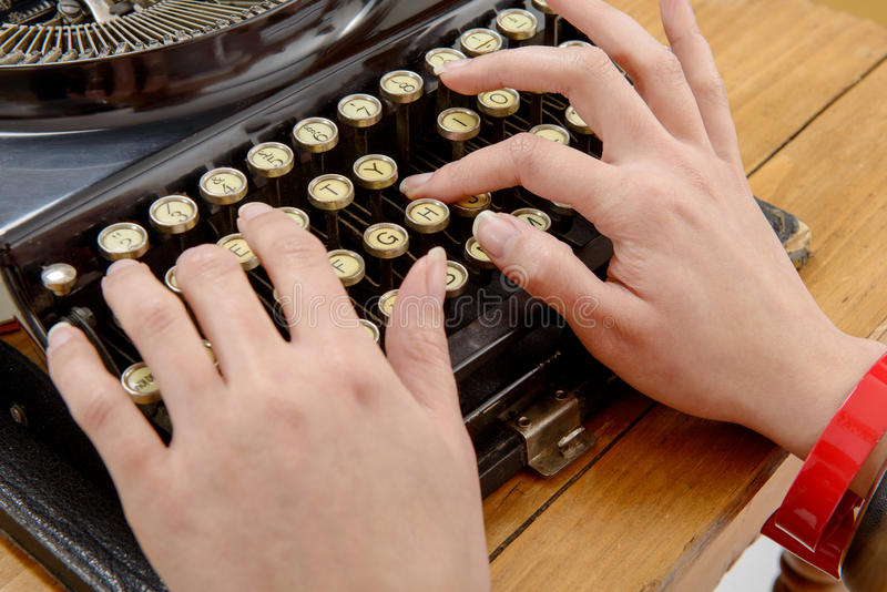 Hands of a young woman with an old typewriter. Closeup of hands of a young woman with an old typewriter stock photos