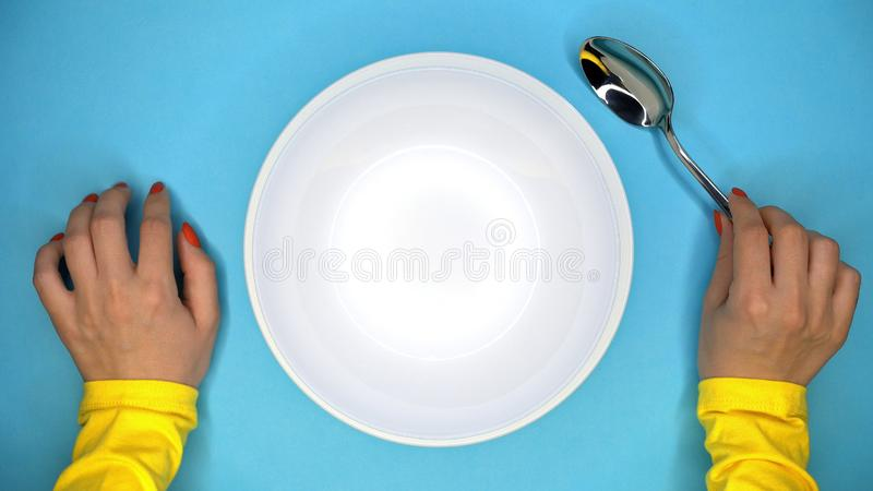 Hands of young woman with spoon. Lady sitting in restaurant and waiting for order. Empty white plate on blue background stock photos
