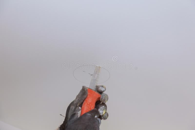 Handsaw cutting circular hole in ceiling. Cutting panels in apartment light drywall repairman work tool install worker construction renovation blade fix royalty free stock photography