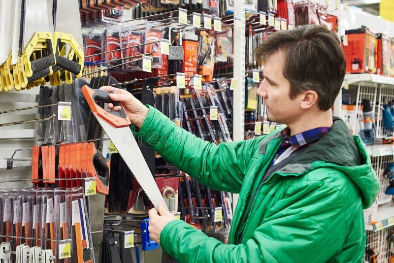 Handsaw de compra del hombre en tienda imagen de archivo libre de regalías