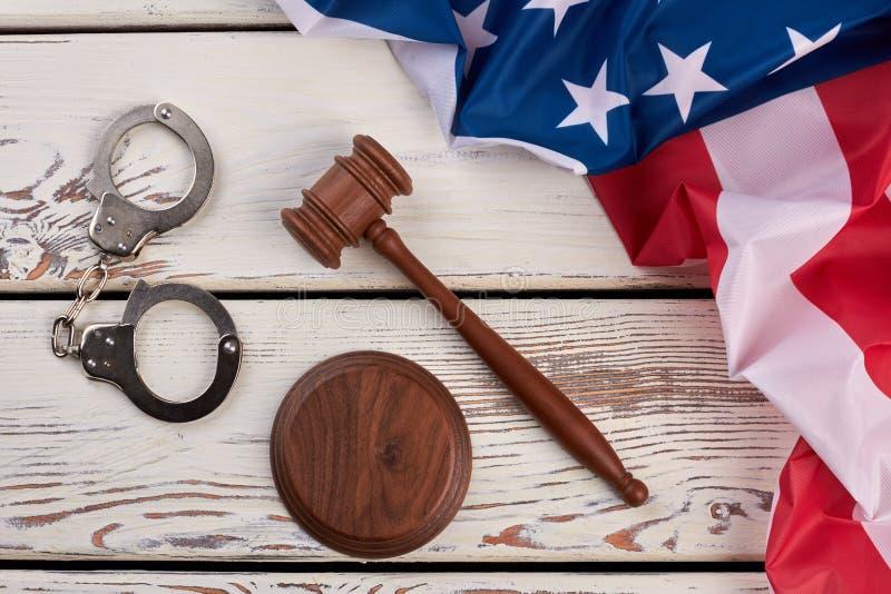 Handschellen, hölzerner Hammer und USA-Flagge lizenzfreie stockfotografie