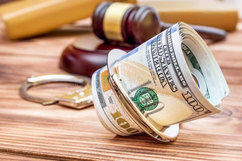 Handschellen mit Geld, Hammer und Büchern lizenzfreie stockfotos