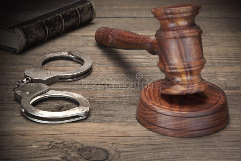 Handschellen, Richter-Gavel And Old-Gesetzbücher auf Holztisch lizenzfreie stockbilder