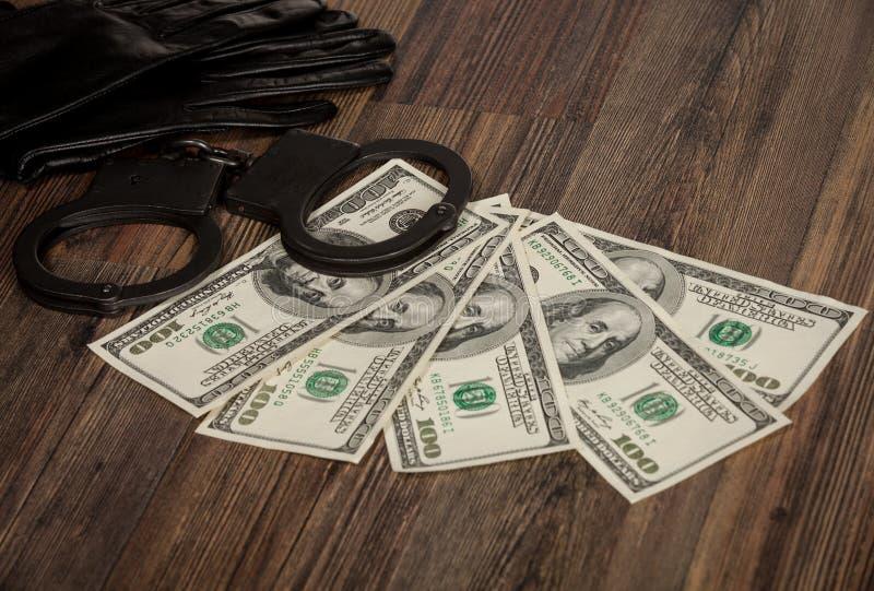 Handschoenen, handcuffs en dollars royalty-vrije stock fotografie