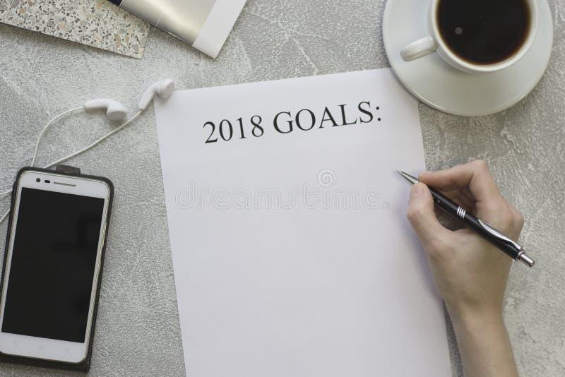 Handschrift 2018 doelstellingen, een mobiele telefoon met hoofdtelefoons en een kop van cofee stock fotografie
