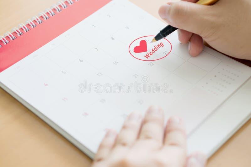 Handschrift im Kalenderplan und in den Münzen Konzept, Hochzeit lizenzfreie stockbilder