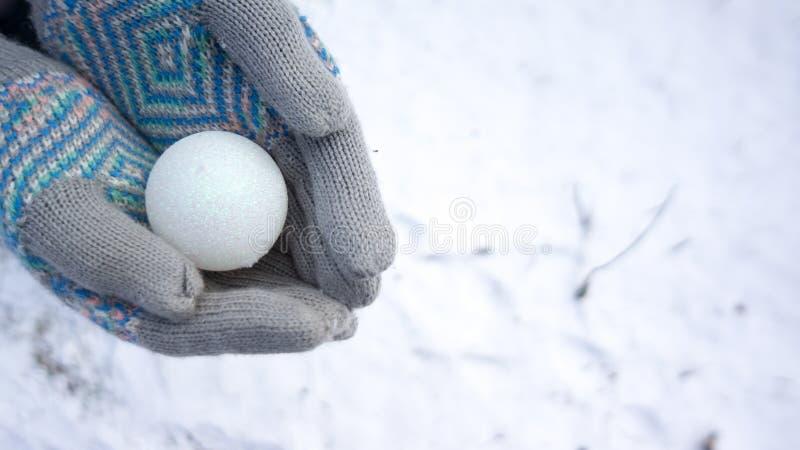 Handschuhe, die Verzierung im Schnee halten stockbild