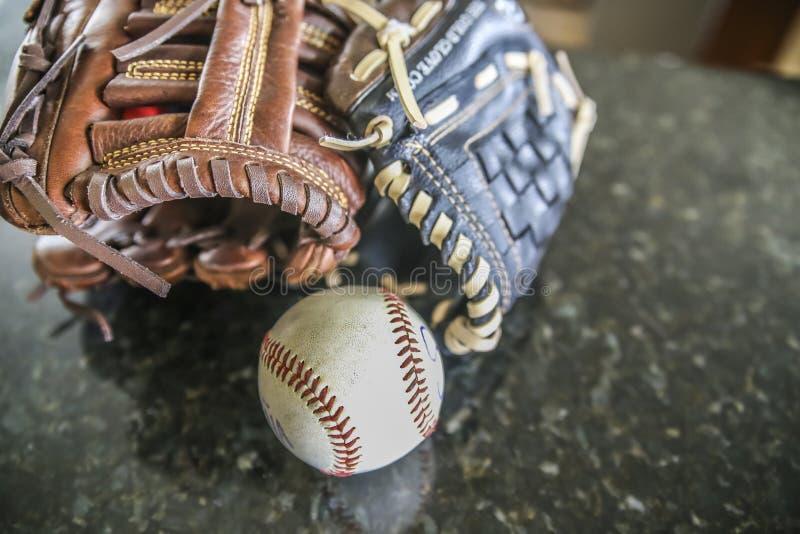 Handschuhe und Ball, die auf einer Tabelle stillstehen stockfotografie