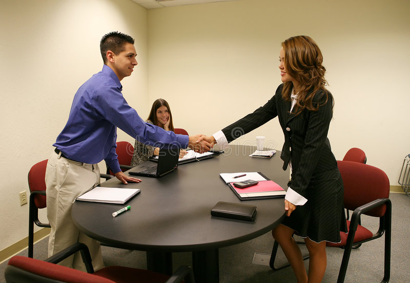 Handshake. A woman shaking a mans hand to conclude a business deal stock photos